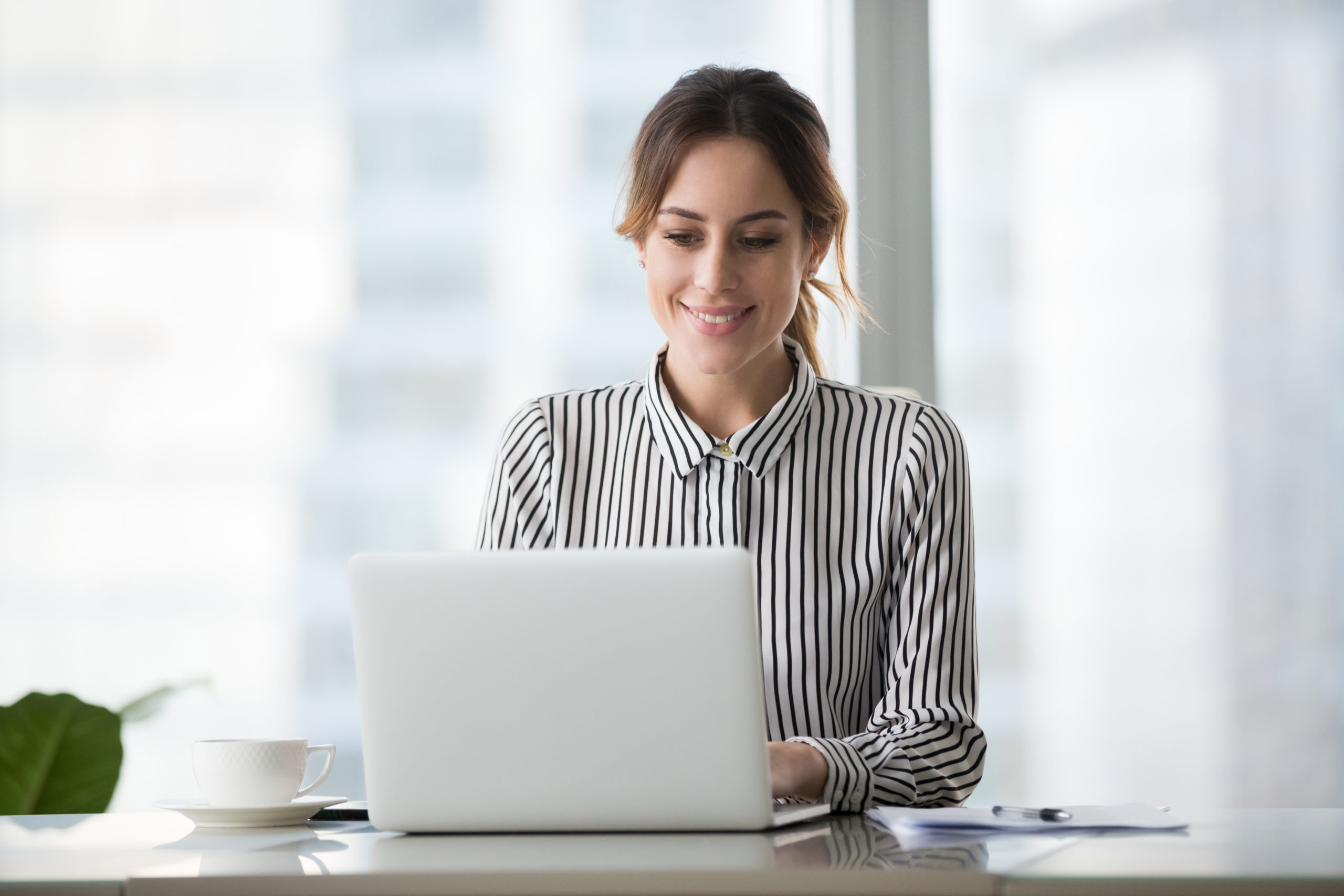 Woman taking part in Webinar sitting in front of computer PC Mac
